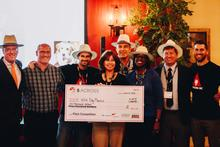 Janelle Molloy (center) accepting the winner's check.