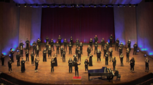 """Photo of UK Choristers physically distanced on Singletary Center stage performing for virtual """"Collage"""""""