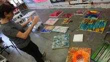 photo of student looking at contemporary paintings on floor - Fine Arts Institute
