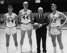 photo of Adolph Rupp (in suit) with basketball players Mike Casey, Dan Issel and Mike Pratt