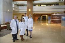 Four people standing in atrium