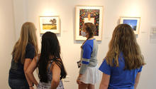 image of students looking at photographs at exhibit.
