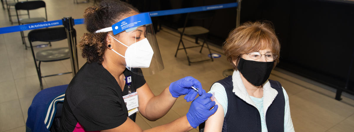 woman receives covid shot in her left arm at UK vaccination clinic