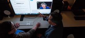 photo of Doug Boyd (right) working with colleague on oral history interview on computer