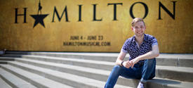 photo of Patrick Garr seated outside The Kentucky Center sign for Hamilton