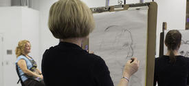 photo of 2 Fine Arts Institute students drawing a model