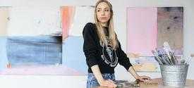 photo of Dana James in her studio with paintings behind her
