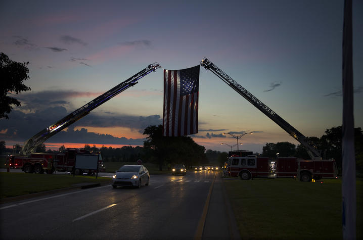 Photo of a massive American flag hanging between two Lexington Fire Department trucks