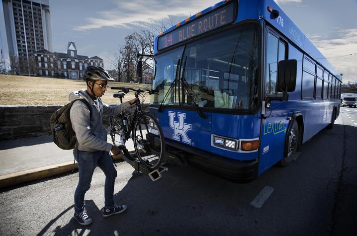 photo of man adding bike to bus