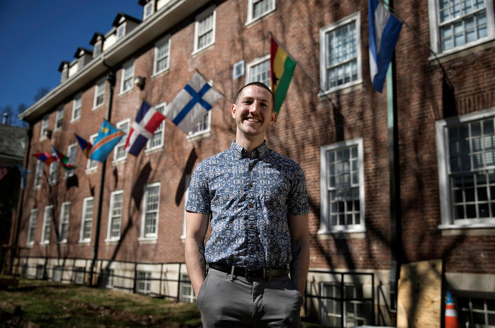 Photo of Trey Cardwell stands in front of a building adorned with flags Photo by Mark Cornelison | UK Photo