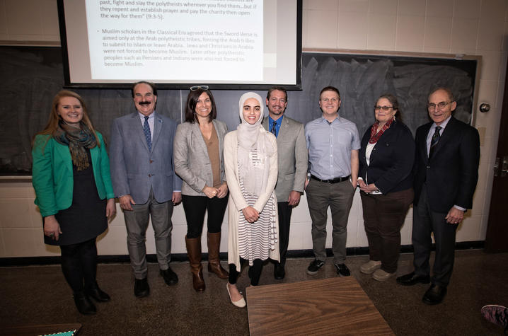 photo of administrators, faculty and mentors with Hadeel Abdallah in front of chalkboad