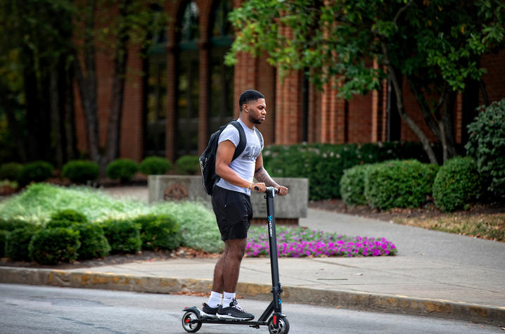 Photo of student riding scooter throughout campus