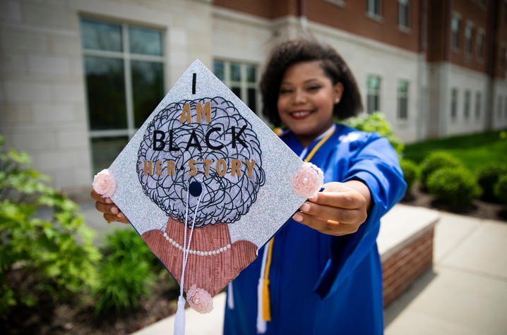 photo of Jazmin Nichols holding her decorated mortarboard outside Woodland Glen II