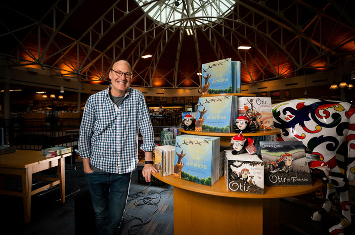photo of Loren Long beside a table display of his books at Joseph-Beth