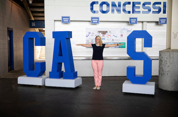 Staff member posing with the CATS sign.