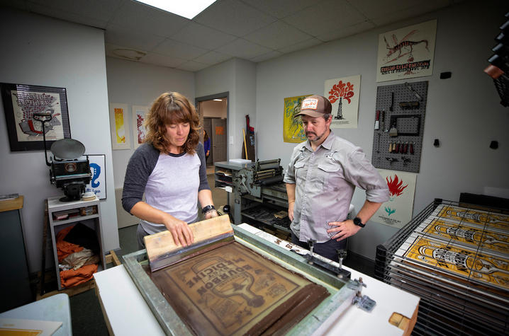 photo of Sara Turner applying ink to print while Brian Turner watches on