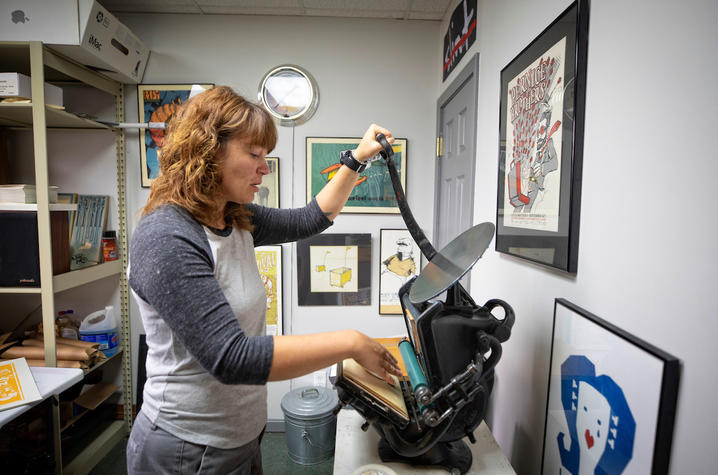 photo of Sara Turner working on a coaster on a small press