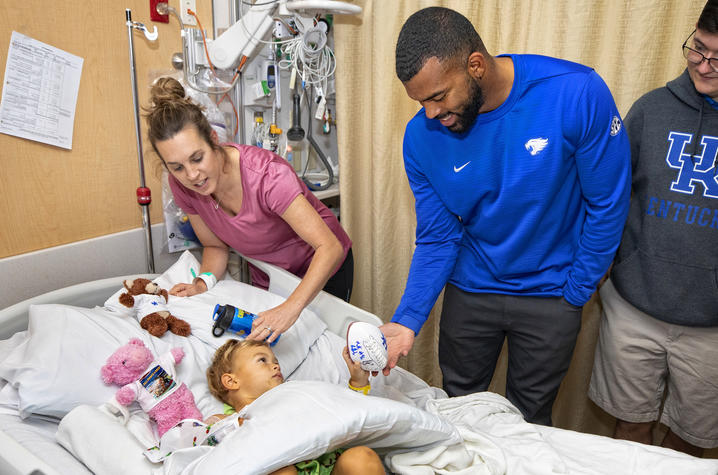 Courtney Love hands football to young patient