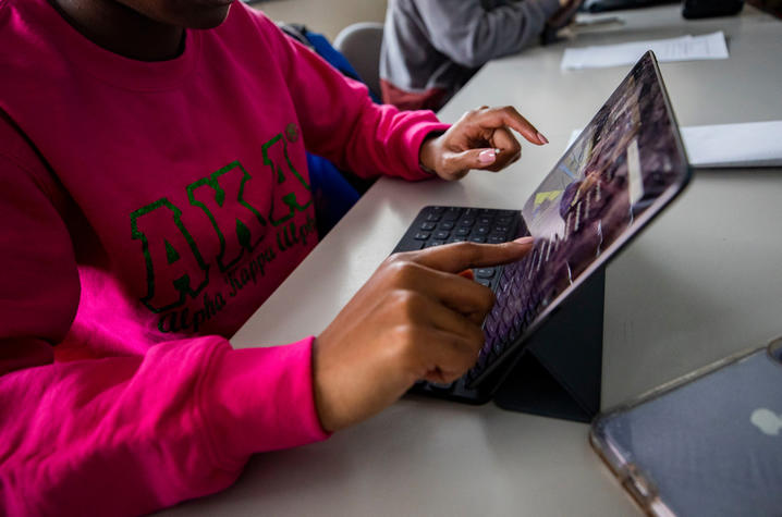 Student in pink AKA shirt works on her iPad.