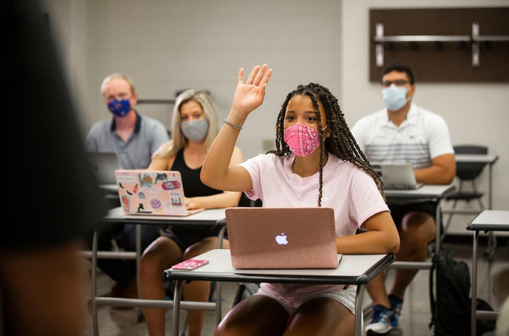 photo of students in class and one raising her hand to ask a question