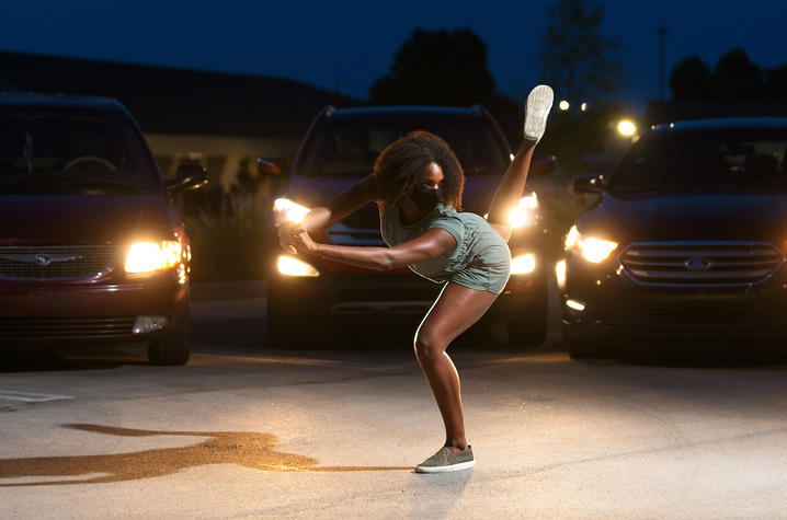 "photo of ""Once Vacant"" dancer performing in parking lot with car lights shining behind her"