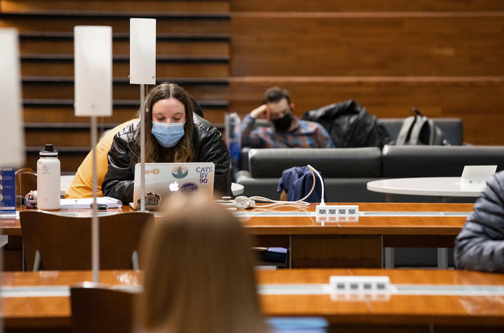 photo of masked student studying in atrium of Gatton College
