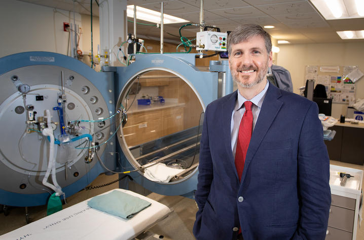 Dr. Kevin Hatton, the division chief of Anesthesiology Critical Care Medicine at UK HealthCare, poses next to the hyperbaric oxygen treatment chamber.