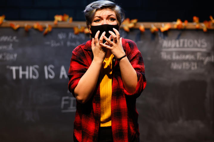 """photo of cast member rehearsing UK Theatre's """"The Thanksgiving Play"""" standing in front of chalkboard"""