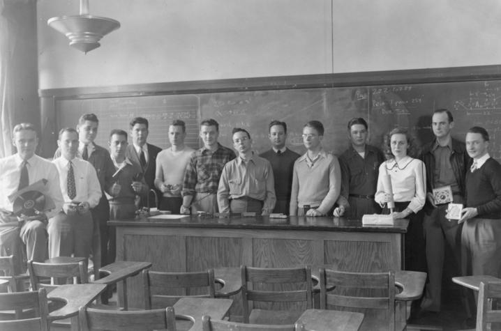 black and white photo of students in a circa 1940 classroom holding item representing area of study