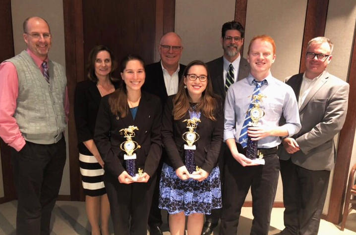 photo of three student winners with trophies and faculty and administrators at 5-Minute Fast Track Research Competition
