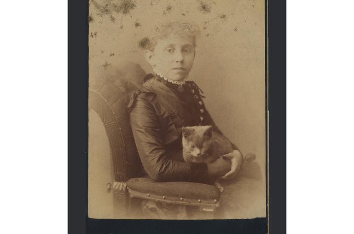 old sepia tone photo of girl seated with cat in her lap
