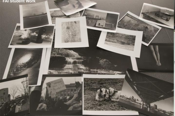 a black and white photo of a pile of black and white photos and a photo of negatives on a lightboard