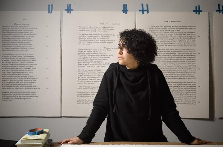 photo of Bethany Collins at table surrounded by work hanging and on table