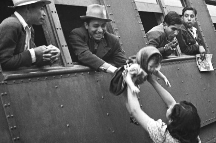 black and white photo of man passing baby out of train window to woman - Braceros Photo Exhibit