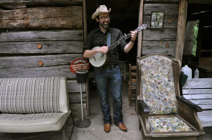 photo of Brett Ratliff on porch with banjo