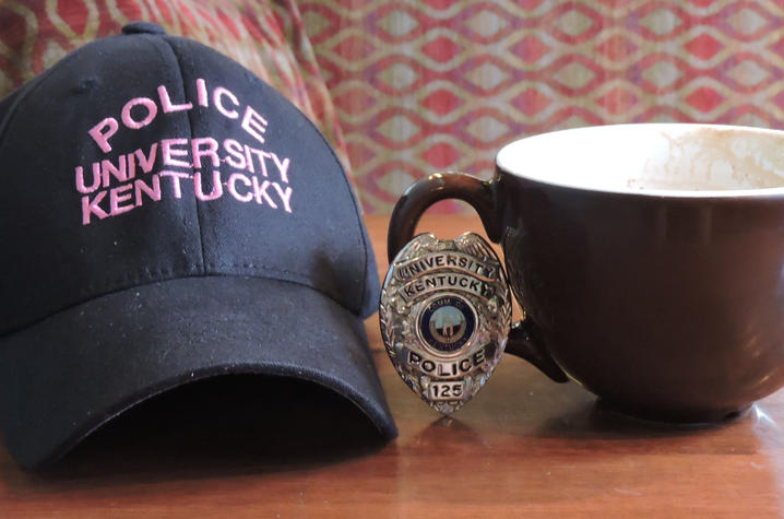photo of hat that says UK Police, a UK Police badge and a coffee cup