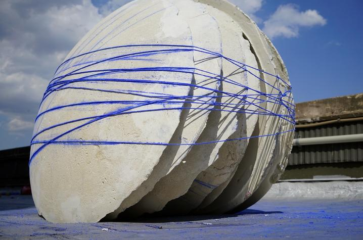 """photo of sculptural piece of multiple concrete disks connected to each other with blue rope titled """"The Ways We Are"""" by Crystal Gregory and Alexa Williams"""