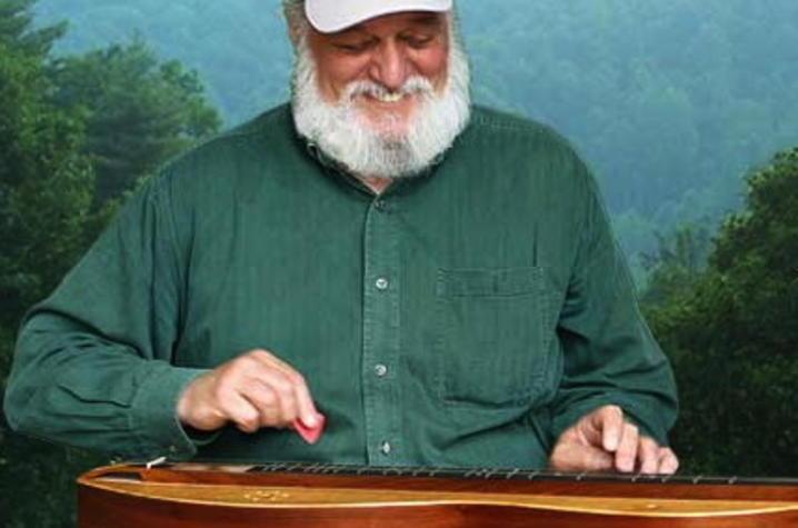 photo of Don Pedi playing dulcimer with mountain view behind