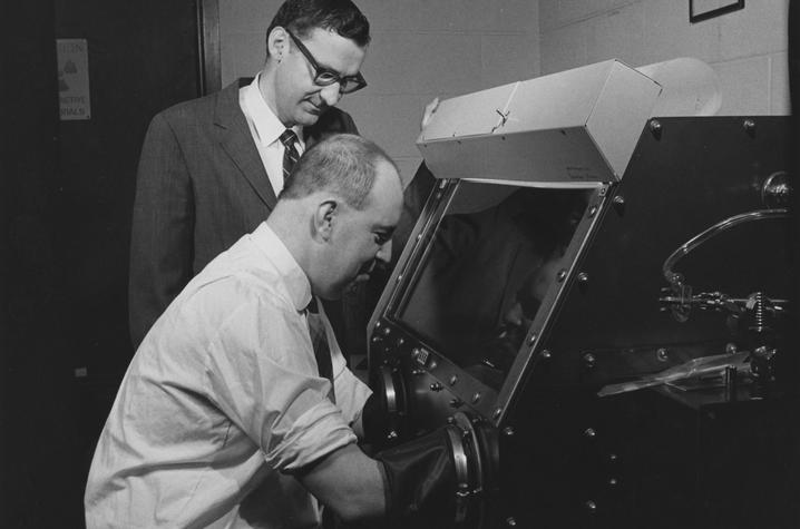 photo of Bill Ehmann and John Morgan studying moon rock
