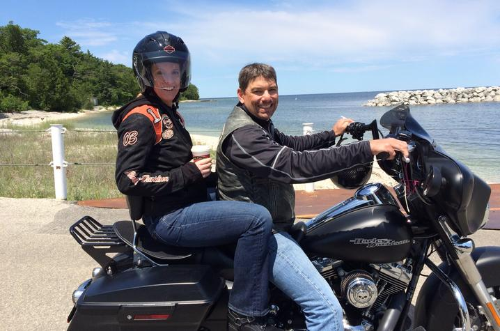 This is a photo of Carl Mattacola and his wife, Kathleen, riding a motorcycle.