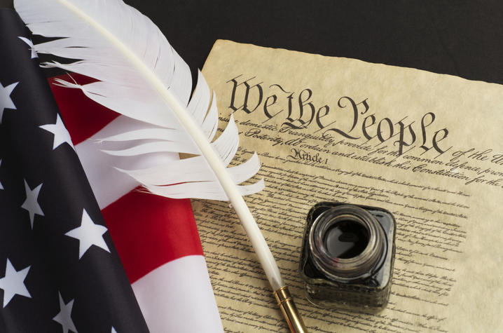 staged photo of copy of Constitution with a quill and bottle of ink and American flag beside of it