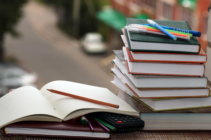 photo of books stacked on a desk with pens and calculator