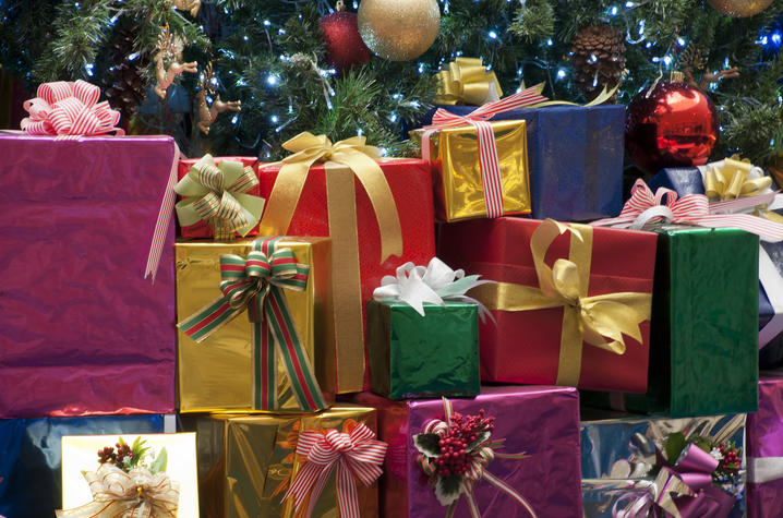 Photo of a pile of wrapped gifts by Christmas tree