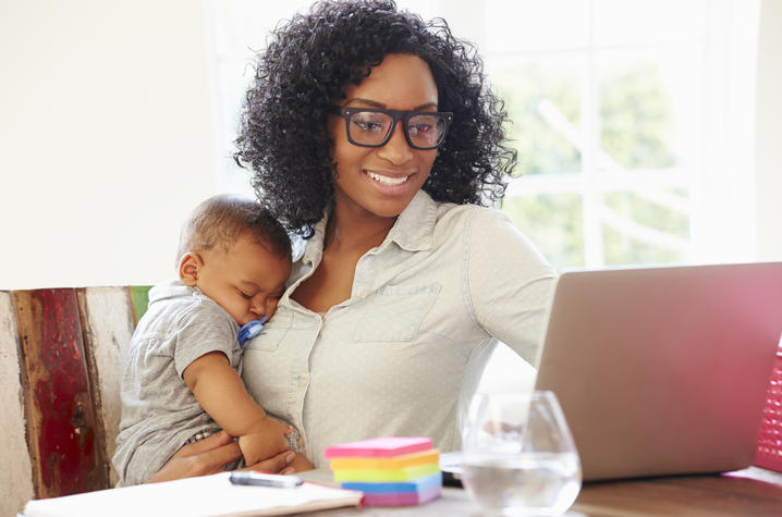 photo of woman working from home while holding a baby