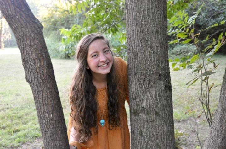 photo of Hannah Thomas posing by tree