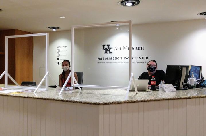 photo of UK Art Museum staff masked and seated behind plexiglass