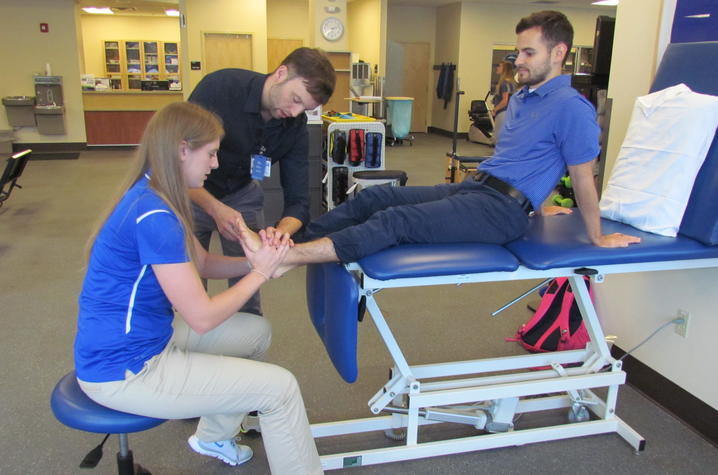 Ryan shows Morgan how to adjust a patient's foot