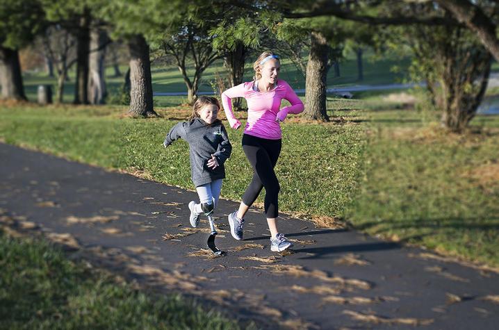 Photo of Carson Swartz running with Katie Eddington, who has a prosthetic leg