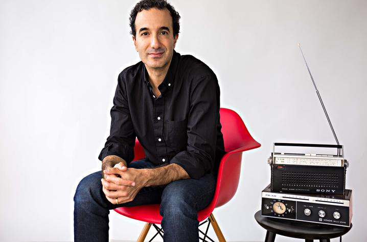 photo of Jad Abumrad seated in red chair next to radio