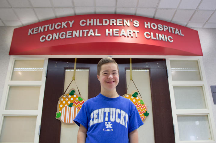 photo of jeremiah in front of the doors to the pediatric heart clinic